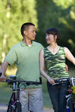Couples entre les bicyclettes souriant - verticale Images stock