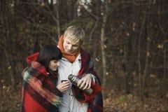 Couples enveloppés dans la couverture ayant le thé chaud Photos stock