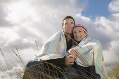 Couples enveloppés dans la couverture dehors photos stock