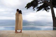 Couples enveloppés dans la couverture regardant la piscine d'infini Photo libre de droits