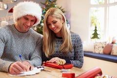 Couples enveloppant des cadeaux de Noël à la maison Photos stock