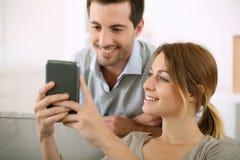 Couples envoyant le message sur le smartphone de la maison Photographie stock libre de droits