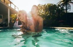 Couples espiègles appréciant dans la piscine Images stock