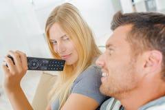 Couples espiègles combattant au-dessus de l'extérieur de TV Photo libre de droits