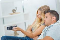 Couples espiègles combattant au-dessus de l'extérieur de TV Photos libres de droits