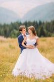 Couples espiègles heureux de mariage sur le champ ensoleillé avec le fond de forêt Images stock