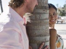 Couples espiègles par le tronc d'arbre Image libre de droits