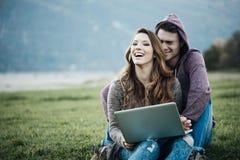 Couples espiègles utilisant un ordinateur portable en nature Photo libre de droits