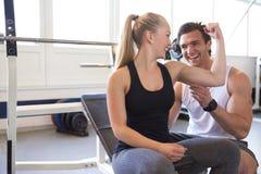 Couples espiègles vérifiant la taille de muscle de biceps dans le gymnase Images stock