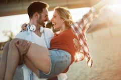 Couples espiègles véritablement heureux ayant l'amusement à la plage Photo stock