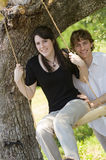 Couples espiègles sur l'oscillation à l'extérieur Photographie stock libre de droits