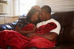 Couples essayant de garder la couverture de dessous chaude à la maison images stock
