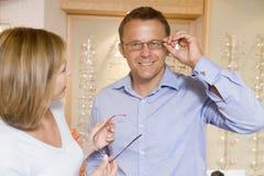 Couples essayant sur des lunettes aux optométristes image stock