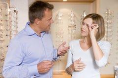 Couples essayant sur des lunettes aux optométristes photographie stock libre de droits