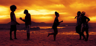 Couples et amis et coureur à la plage sur le coucher du soleil Photographie stock