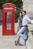 Couples et cadre rouge de téléphone à Londres, Angleterre Photographie stock libre de droits