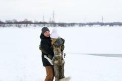 Couples et chien se tenant sur la neige Photos stock