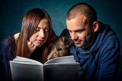 Couples et leur chien lisant un livre photographie stock