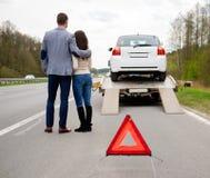 Couples et voiture cassée sur une route Photos libres de droits