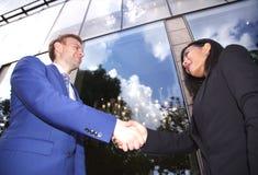 Couples ethniques multi d'affaires se serrant la main Photo stock