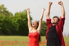 Couples euphoriques soulevant des bras dans le pays Images libres de droits