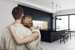 Couples européens dans la cuisine moderne Photographie stock