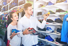 Couples examinant de diverses espadrilles dans le magasin de sports Photo libre de droits
