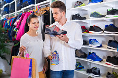 Couples examinant de diverses espadrilles dans le magasin de sports Photographie stock libre de droits