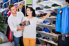 Couples examinant de diverses espadrilles dans le magasin de sports Photos stock