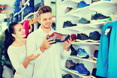 Couples examinant de diverses espadrilles dans le magasin de sports Photo stock