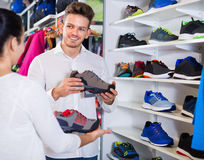 Couples examinant de diverses espadrilles dans le magasin de sports Images stock