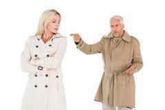 Couples fâchés combattant dans des manteaux de fossé Image libre de droits