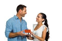 Couples face à face tenant le modèle de maison Image stock
