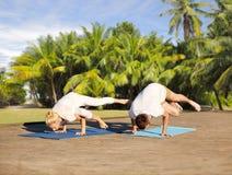 Couples faisant à yoga la grue latérale poser dehors Image libre de droits