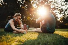 Couples faisant étirant des exercices en stationnement Image stock