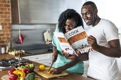 Couples faisant cuire dans la cuisine ensemble Images libres de droits