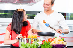 Couples faisant cuire des pâtes dans la cuisine domestique Photographie stock