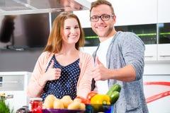 Couples faisant cuire des pâtes dans la cuisine domestique Photo libre de droits