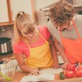 Couples faisant cuire en livre de cuisine de lecture de cuisine Photo stock
