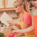 Couples faisant cuire en livre de cuisine de lecture de cuisine Image stock