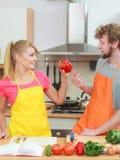 Couples faisant cuire en livre de cuisine de lecture de cuisine Images stock