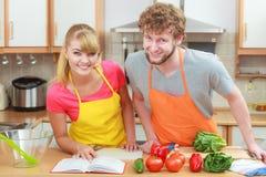 Couples faisant cuire en livre de cuisine de lecture de cuisine Photographie stock libre de droits