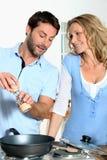 Couples faisant cuire ensemble à la maison images libres de droits
