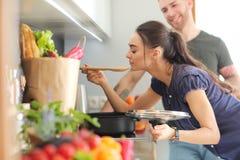 Couples faisant cuire ensemble dans leur cuisine à la maison Photographie stock libre de droits