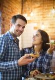 Couples faisant cuire et mangeant ensemble à la cuisine Photos libres de droits