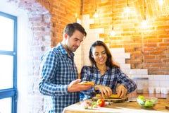 Couples faisant cuire et mangeant ensemble à la cuisine Photographie stock