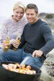 Couples faisant cuire le barbecue sur la plage d'A Photos stock