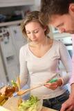Couples faisant cuire le dîner ensemble Image libre de droits