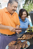 Couples faisant cuire sur un barbecue photo libre de droits