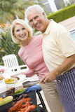 Couples faisant cuire sur un barbecue Photos stock